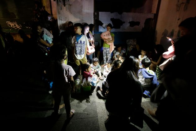 Evacuees gather beside a road as Taal Volcano erupts Sunday Jan. 12, 2020, in Tagaytay, Cavite province,...