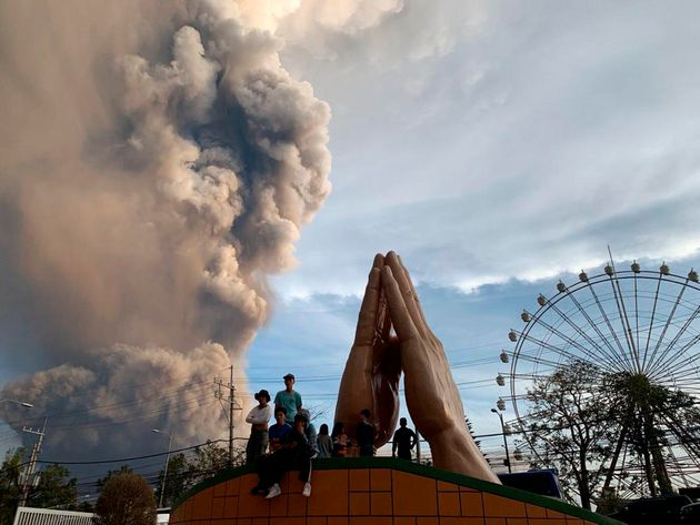 People watch as the Taal volcano spews ash and smoke during an eruption in Tagaytay, Cavite province...