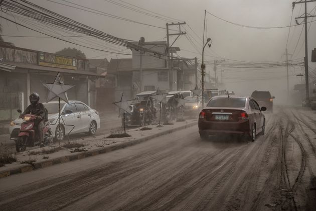 Motorists drive through a road covered in volcanic ash from Taal Volcano's eruption in Lemery, Batangas...