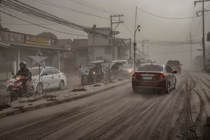 Motorists drive through a road covered in volcanic ash from Taal Volcano's eruption in Lemery, Batangas province, Philippines