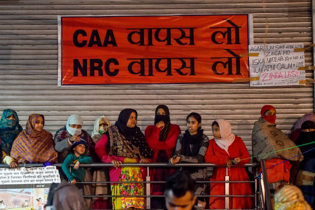 Protesters stand in front of a banner during a demonstration at Shaheen Bagh area. The photo was taken...
