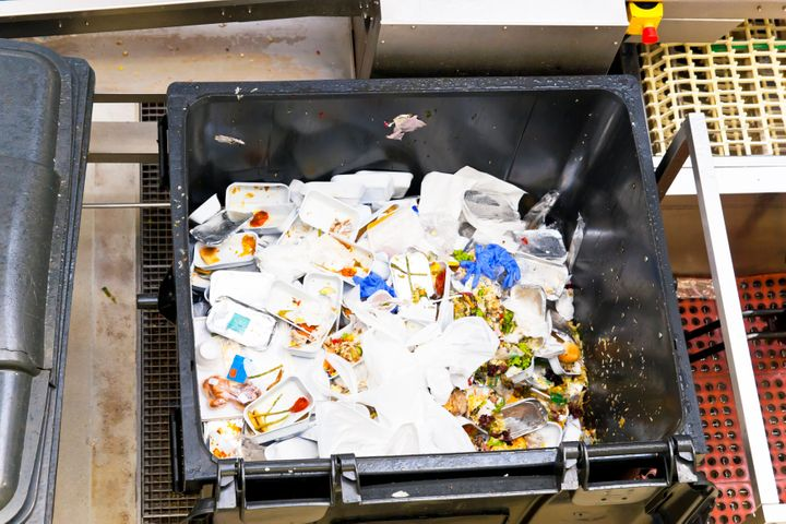 Leftovers of airline food in a large waste container from in-flight service.