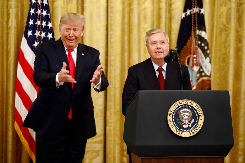 President Donald Trump gestures as Sen. Lindsey Graham (R-S.C.) speaks in the East Room of the White House on Nov. 6, 2019. G