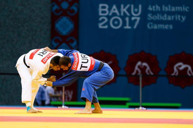 Saeid Mollaei(in white) of Iran and Gulduren Ilker (in blue) of Turkey compete for the men's judo...