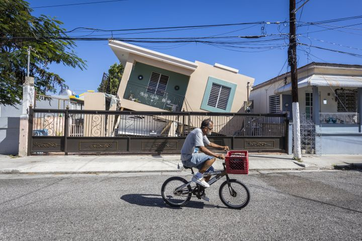 A man rides his bike in front of a collapsed house after a 6.4-magnitude earthquake hit Guanica, Puerto Rico, on Jan. 11, 202