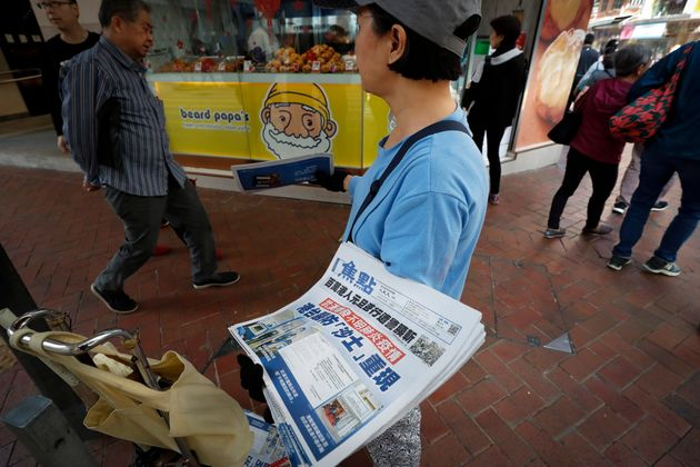 A vendor gives out copies of newspaper with a headlines of