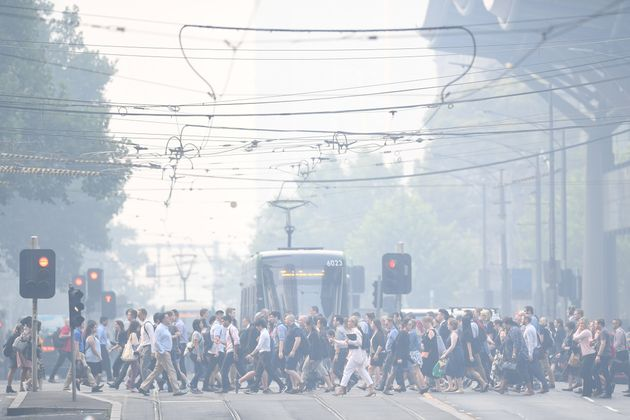 Morning commuters are seen through smoke haze from bushfires in Melbourne.