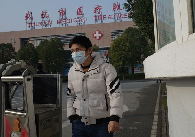 A man leaves the Wuhan Medical Treatment Centre, where a man who died from a respiratory illness was...