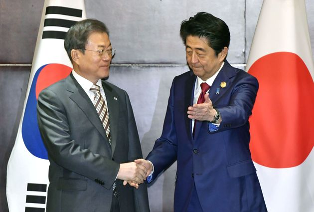 Japan's Prime Minister Shinzo Abe shakes hands with South Korea's President Moon Jae-in during their...