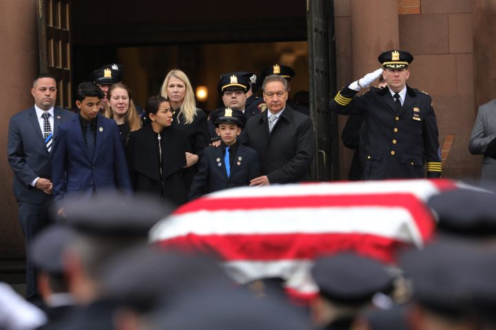 Family members watch as the casket for New Jersey Detective Joseph Seals is brought out of a church during his funeral on Dec