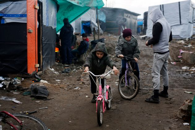 Afghan children ride their bicycles in a makeshift migrants camp near Calais, France, in February