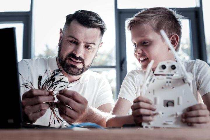 Un padre y un hijo construyen juntos un robot.
