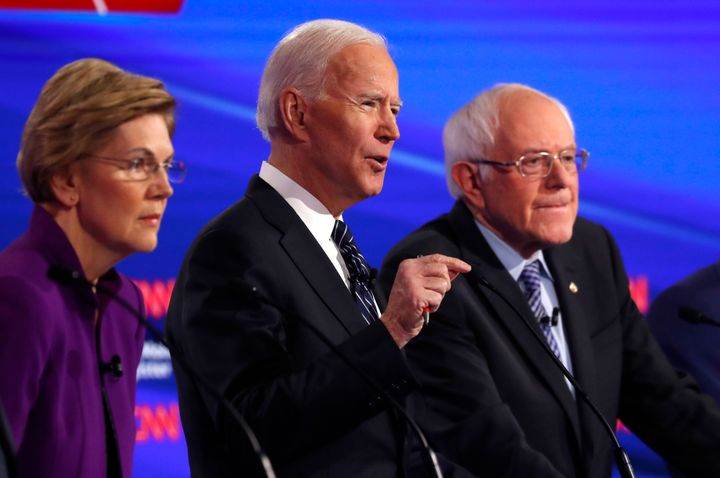 Sens. Elizabeth Warren (D-Mass.) and Bernie Sanders (I-Vt.) listen as former Vice President Joe Biden speaks during the Democ