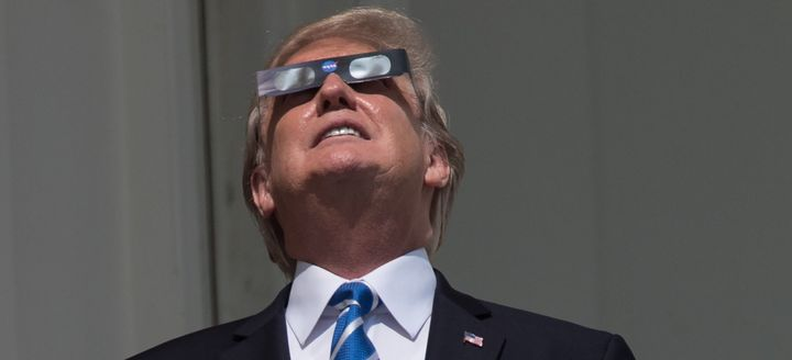 President Donald Trump looks up at the partial solar eclipse from the balcony of the White House on August 21, 2017.