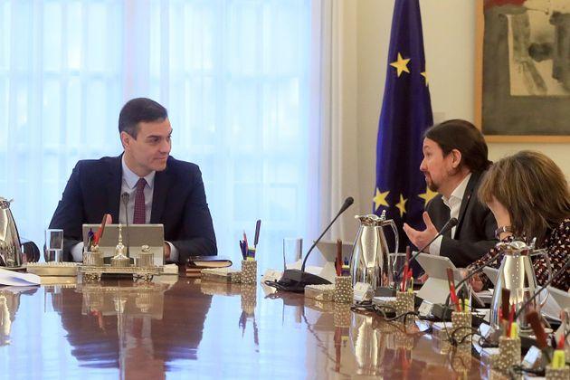 El presidente del Gobierno, Pedro Sánchez (i), conversa con el vicepresidente de Derechos Sociales y...