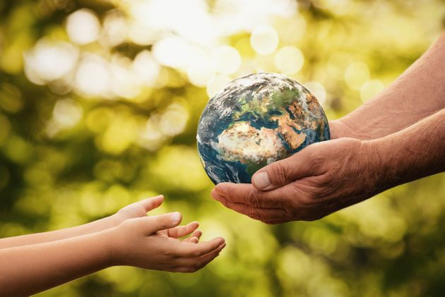 Close up of senior hands giving small planet earth to a child over defocused green background with copy