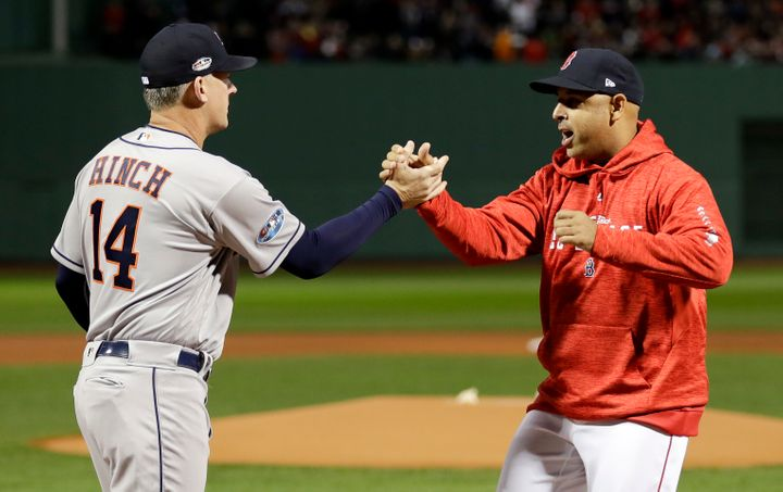 Houston Astros manager AJ Hinch, left, and Boston Red Sox manager Alex Cora shake Hanes before Game 1 of a baseball American