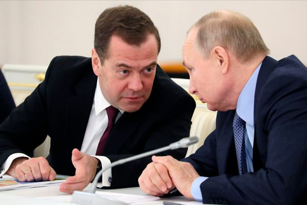 Russian President Vladimir Putin listens to Dmitry Medvedev during the State Council meeting on the agricultural...