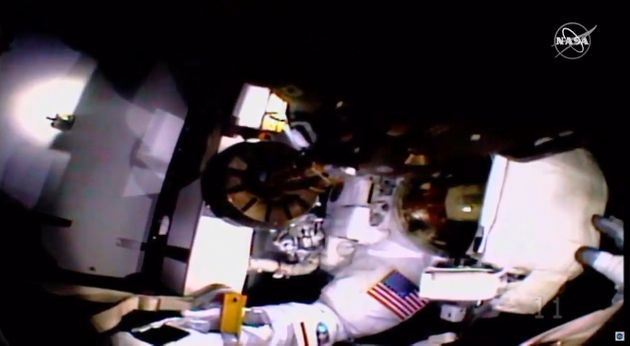 In this image taken from NASA video, NASA astronaut Jessica Meir holds the helmet of fellow astronaut...