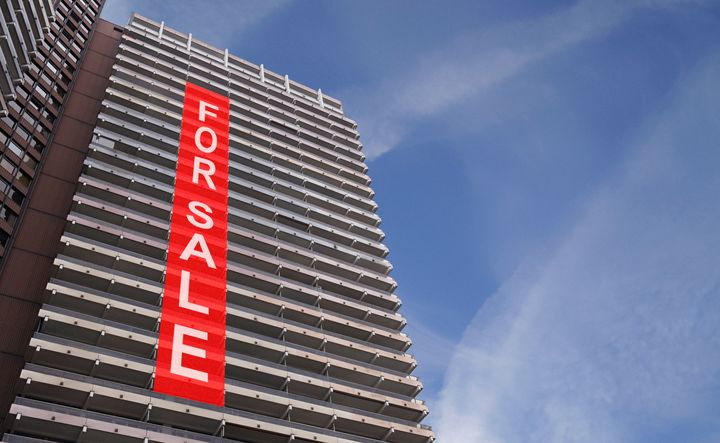 A stock photo of a for-sale sign on a condo building.