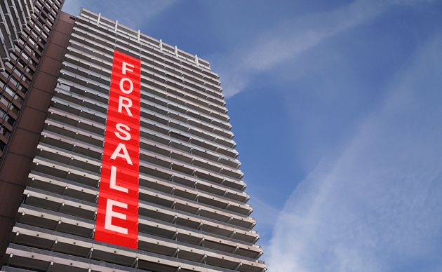 A stock photo of a for-sale sign on a condo