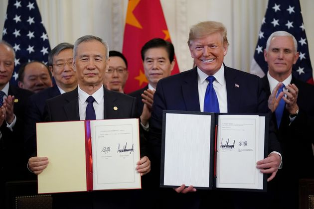 U.S. President Donald Trump stands Chinese Vice Premier Liu He after signing