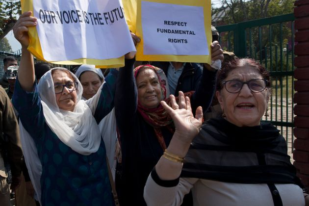 A small group of women under the banner of 'Women of Kashmir', hold placards during a peaceful...