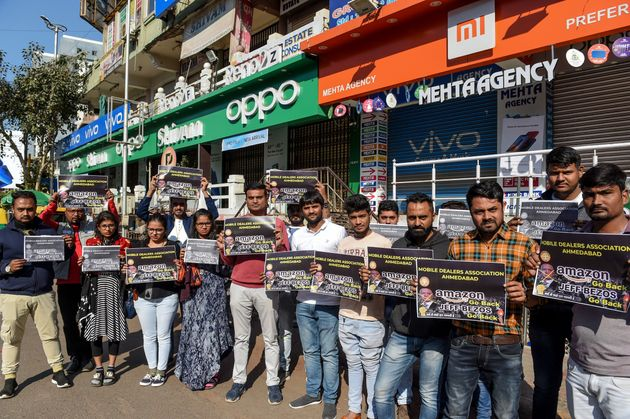 Mobile dealers and members of Ahmedabad Mobile Dealer's Association hold placards as they protest against...