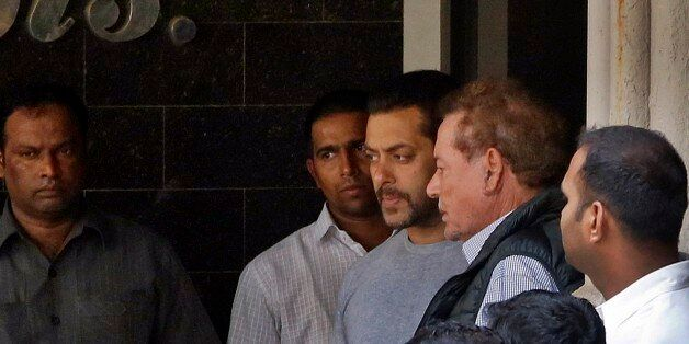 Bollywood actor Salman Khan, center, and his father Salim Khan, second right, come out of their residence...