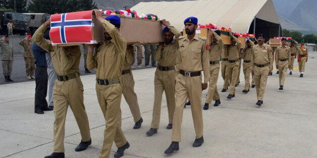Pakistani soldiers carry the caskets of victims of a helicopter crash to a military plane prior to their...