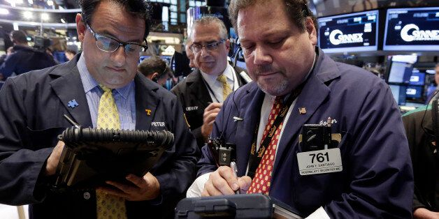 Traders Peter Costa, Kenneth Polcari, and John Santiago, left to right, work on the floor of the New...