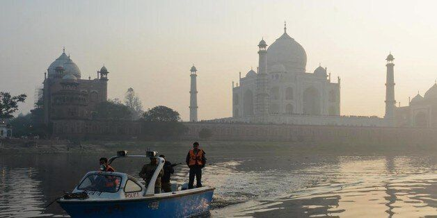The historic Taj Mahal monument is pictured as a police patrol boat moves over the Yamuna river in Agra...