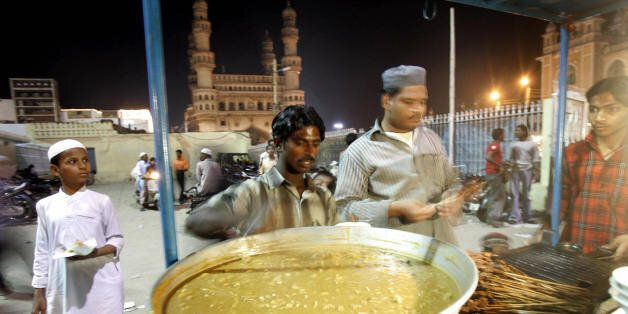 HYDERABAD, INDIA: An Indian vendor prepares kebabs and non-vegetarian delicacies in his stall outside...