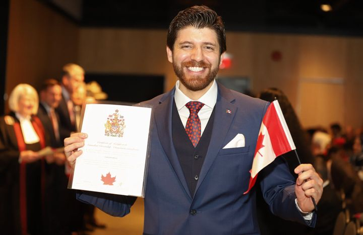 Peace by Chocolate founder and Syrian refugee Tareq Hadhad smiles for the camera as he holds his certificate of Canadian citizenship and a Canadian flag in Halifax on Wednesday.