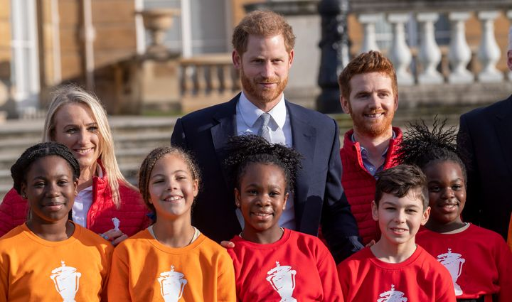 Harry poses with children from a local school after watching them play rugby in the Buckingham Palace gardens before the Rugb