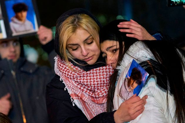 Mourners are seen here in Toronto on Jan. 10 as they console one another during a vigil for the victims...