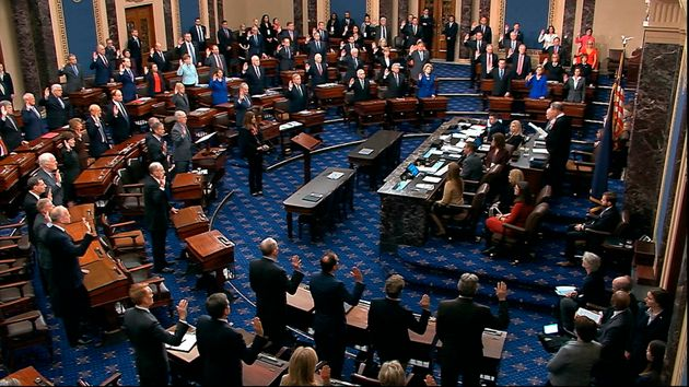 U.S. Supreme Court Chief Justice John Roberts swears in members of the Senate for the impeachment trial...