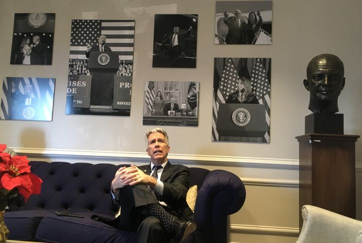 Walsh waits in vain to visit top RNC officials beneath a wall of photos devoted to President Donald Trump.