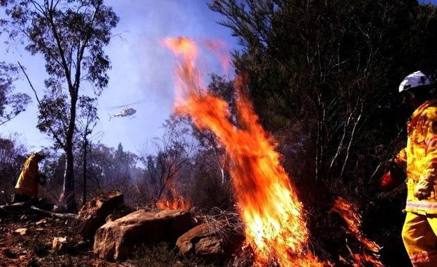 Firefighters drop incendiary devices from a helicopter during a hazard reduction burn off Weddin Mountain...