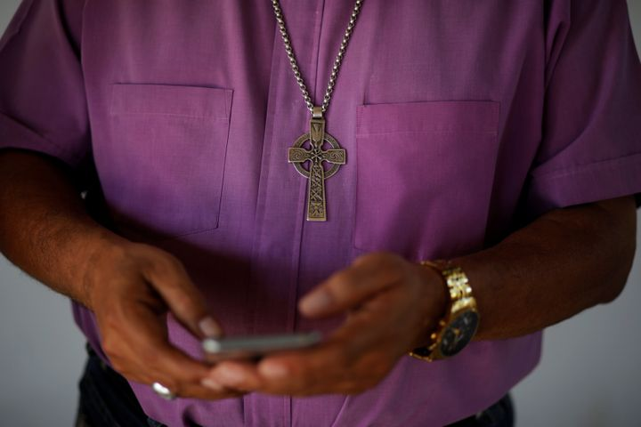 Bishop David Alvarado, of the Anglican Episcolpal Church in El Salvador, checks messages on his cellphone after an interview