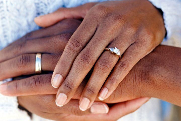 結婚指輪をした手を重ねるカップル イメージ写真