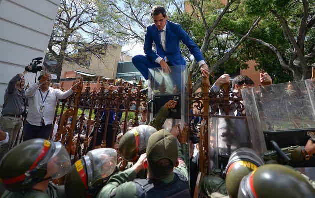El presidente de la Asamblea Nacional de Venezuela, Juan Guaidó, trepa una valla en un intento...