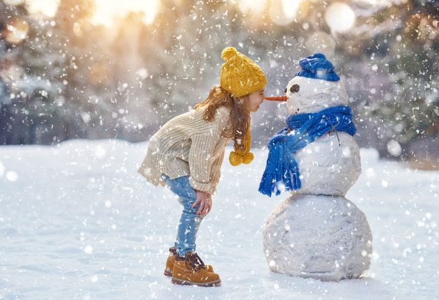happy child girl plaing with a snowman on a snowy winter