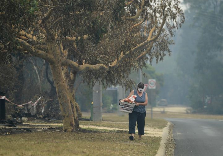 A local walks with smoke mask on in Mallacoota, Victoria.