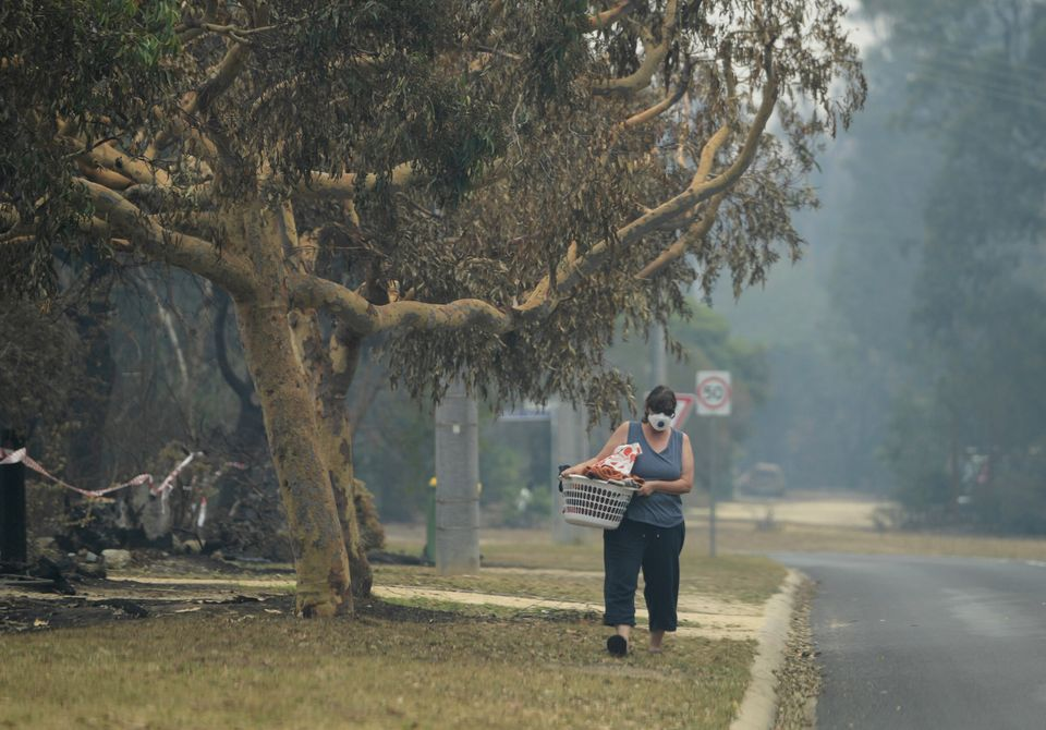 A local walks with smoke mask on in Mallacoota,