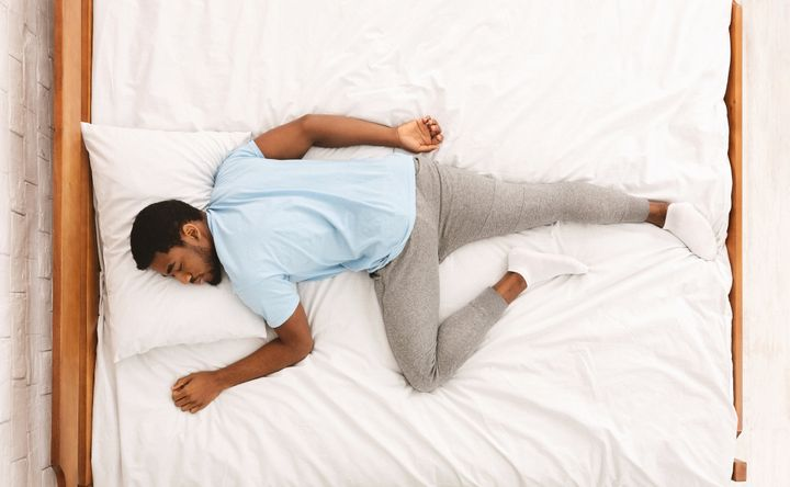 Comfortable pose for sleep. Black millennial guy sleeping, lying on stomach in bed, top view