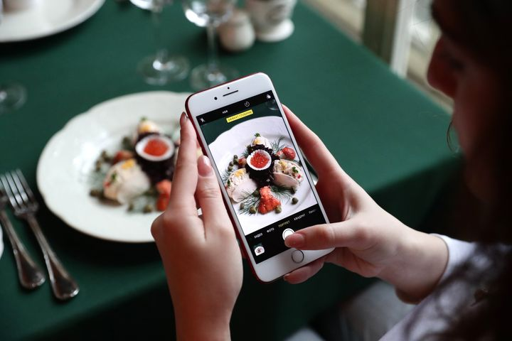 MOSCOW, RUSSIA - DECEMBER 12, 2019: A woman uses a smartphone to take a picture of Olivier salad (Russian salad) in the Pushkin Cafe at Tverskoi Boulevard. Image used for representational purposes only.
