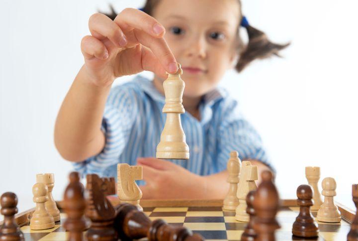 Una niña pequeña jugando al ajedrez.