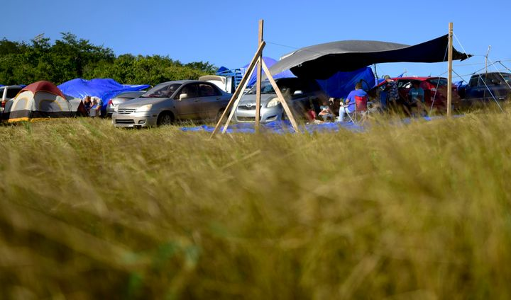 In this Friday, Jan. 10 photo, people shade themselves under a tarp on a private hay farm where residents from the Indios nei