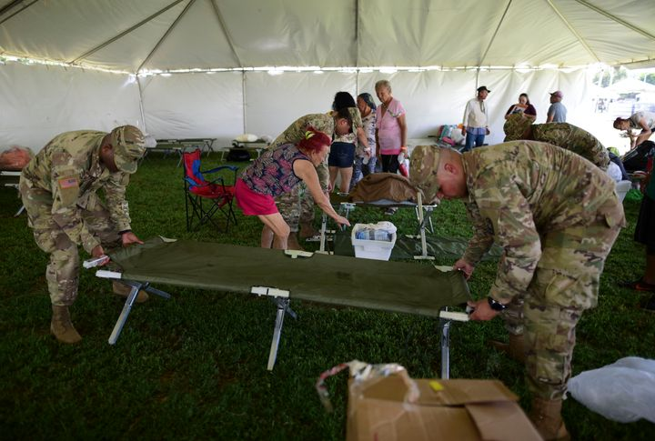Members of the US army reserve assemble a cot as they set up a tent city to house hundreds of people displaced by earthquakes
